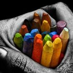 Crayons in the hands of the artist