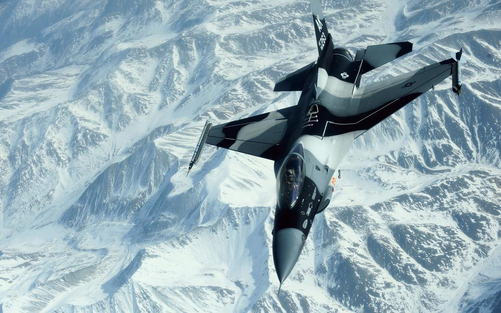 Fighter over snowy peaks