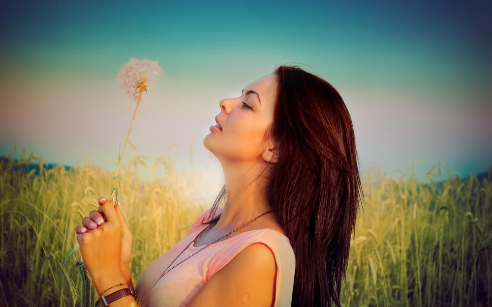 Girl in a field with a dandelion