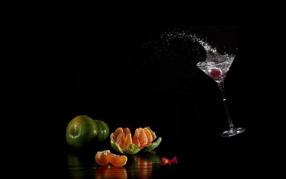 A glass with one next to fruit